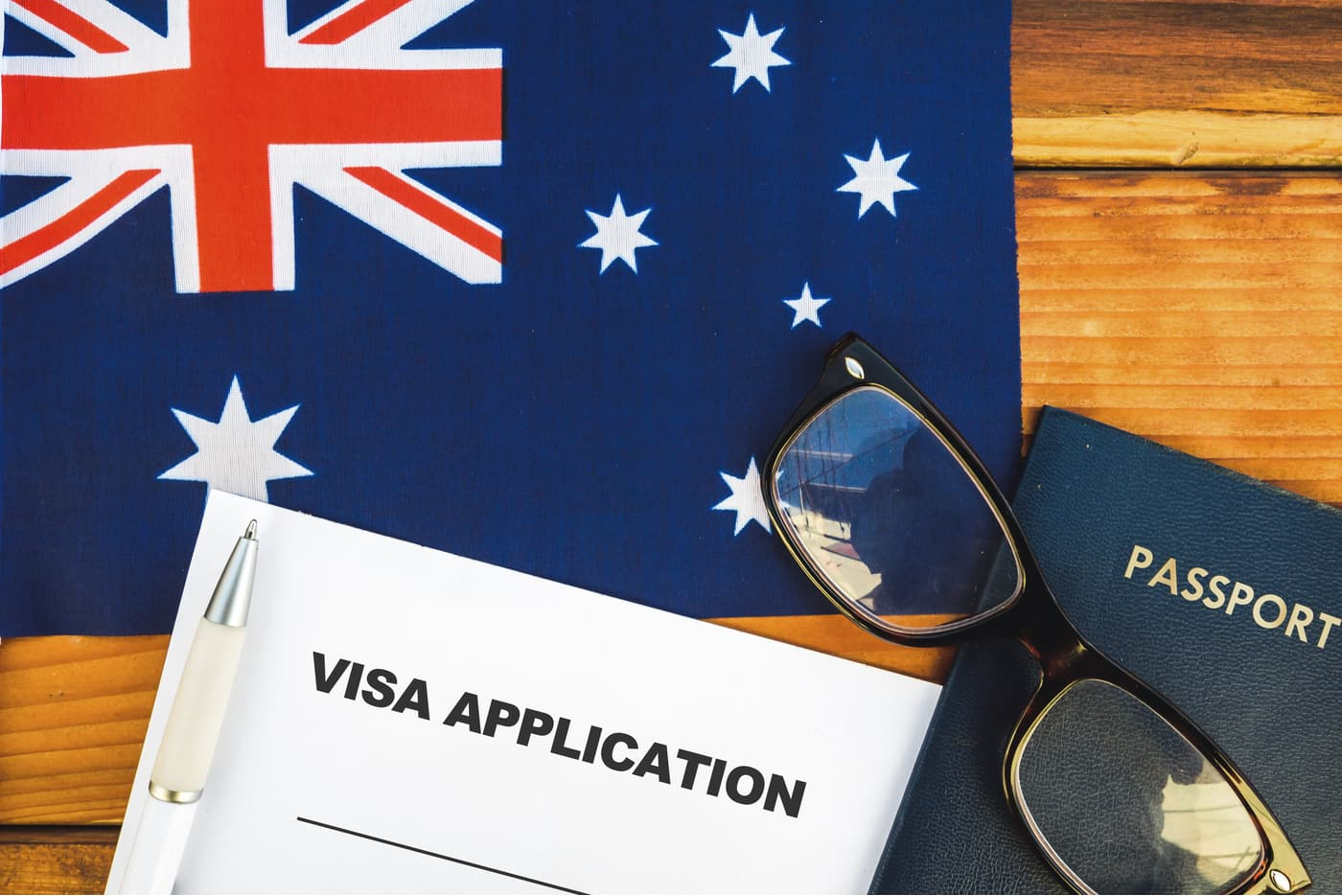 Australian flag with visa application and passport on wooden table