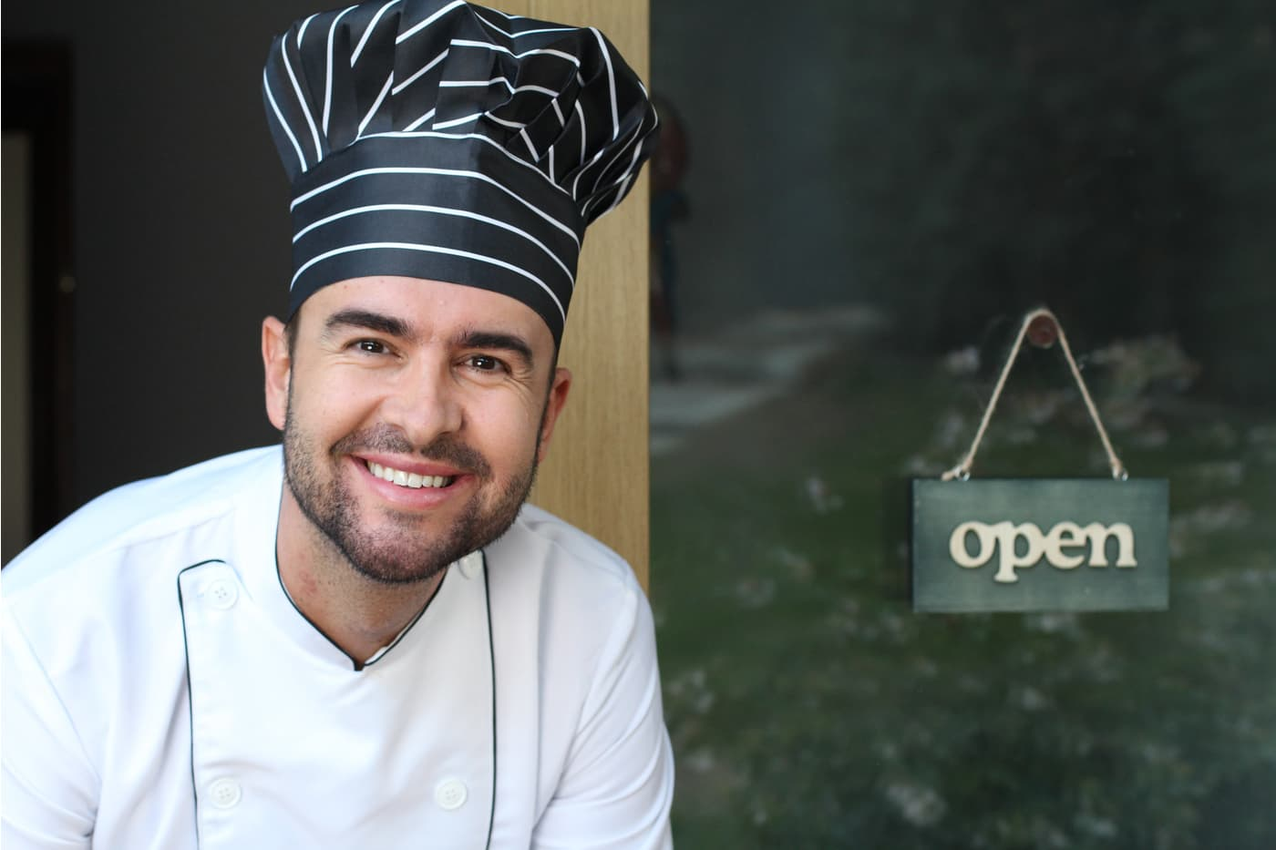 Chef with open sign in the background