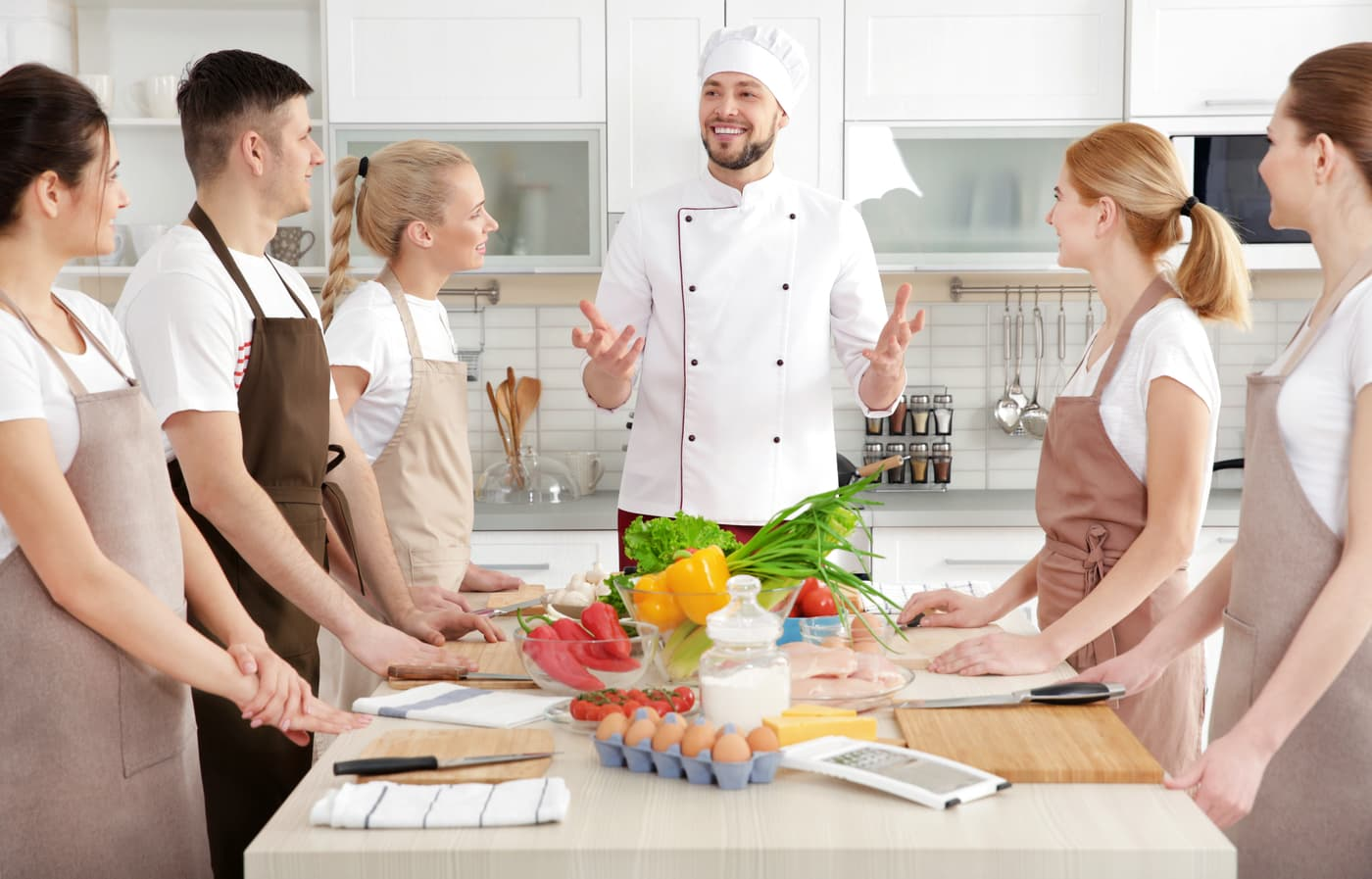 Head chef and students learning to become chefs