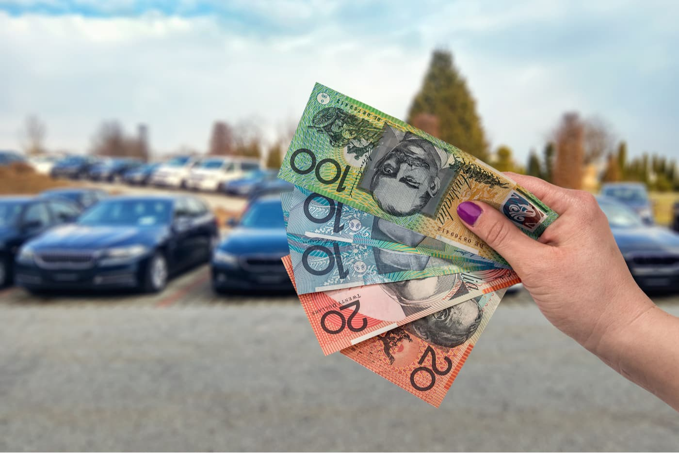 Woman holding up Australian dollars on parking lot background
