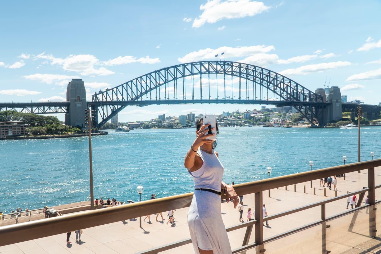 Woman taking selfie in front of the Sydney Harbor Bridge